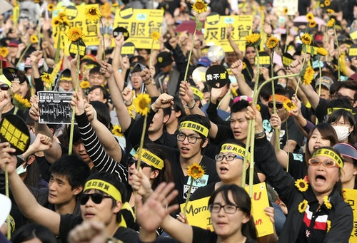 Demonstrators holding sunflowers shout slogans in front of the Presidential Office in Taipei