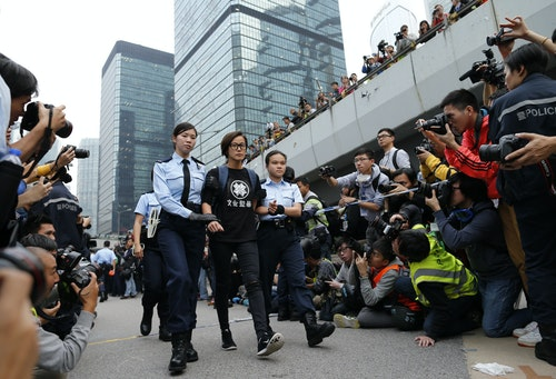 Singer and actress Ho is taken away by policewomen from an area previously blocked by pro-democracy supporters, outside the government headquarters in Hong Kong