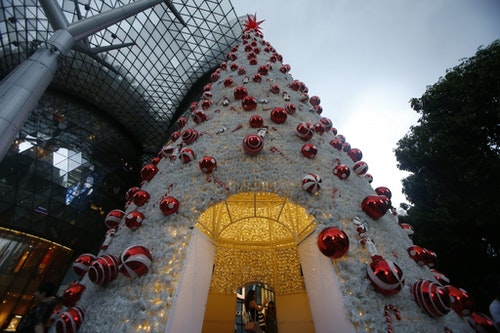 People take pictures inside a Christmas tree along Orchard Road in Singapore