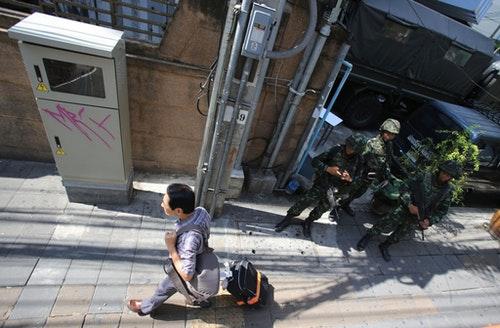 一名旅客在去年泰國五月政變時,經過戒嚴維護秩序的軍人,形成對比。Photo Credit:AP/ 達志影像