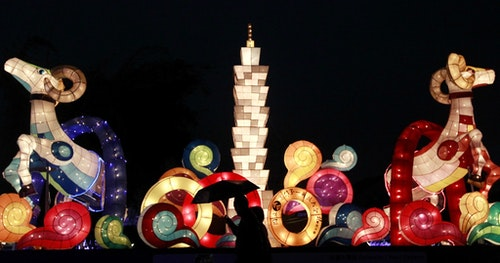 People walk in front of a lantern depicting the Taipei 101 skyscaper, at the Taipei Lantern Festival