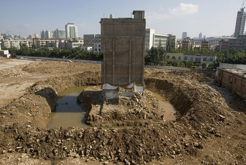 """Owner Zhao Xing, 58, collects water near his partially demolished """"nail house"""", the last house in the area, at a construction site in Kunming"""