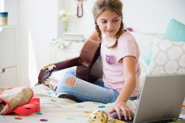 Girl (12-13) playing guitar and using laptop