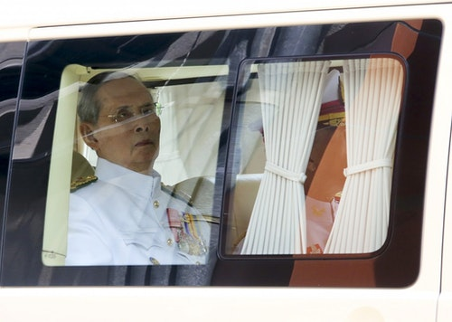 Thailand's King Bhumibol sits in a vehicle as he leaves Siriraj Hospital for the Grand Palace to join a ceremony marking coronation day in Bangkok