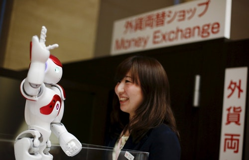 一位銀行行員正在跟機器人Nao互動。人型機器人Nao是由法國Aldebaran Robotics開發,在日本三菱東京UFJ銀行中,他能使用日文、英文、中文提供基本的銀行資訊服務。Photo Credit: Reuters /  達志影像