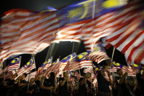 Locals from Sabah wave Malaysian flags during the Malaysia Day celebrations marking Sabah's entry into Malaysia, in Kota Kinabalu