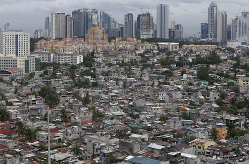 A poor residential district and squatter colonies are overlooked by high rise residential and commercial buildings in Taguig