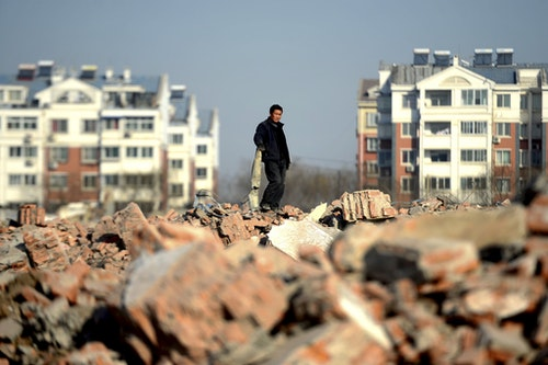 A man looks on as he collects recyclable materials at an area where old residential buildings are being demolished to make room for new ones, in Jinan