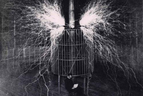 特斯拉實驗室的儀器發出閃光而特斯拉端坐其中  Photo Credit: Tesla Memorial Society of New York