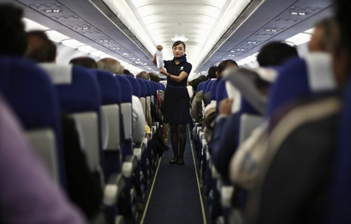 Flight attendants holding up safety information cards and demonstrating safety procedures in the aisle. |Photo Credit: REUTERS