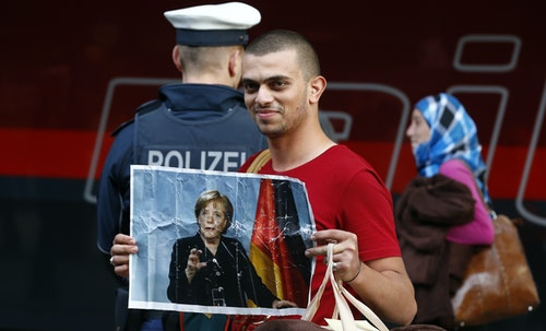 A migrant holds a portrait of German Chancellor Angela Merkel after arriving to the main railway station in Munich