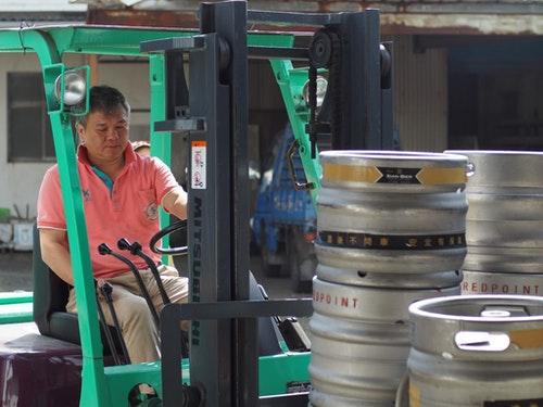 將一桶一桶剛填裝好的啤酒送上貨車的曾老闆。Photo Credit: Alan Chiang