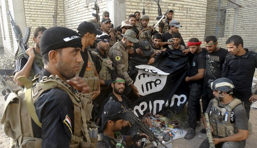Iraqi security forces hold an Islamist State flag which they pulled down at the University of Anbar, in Anbar province