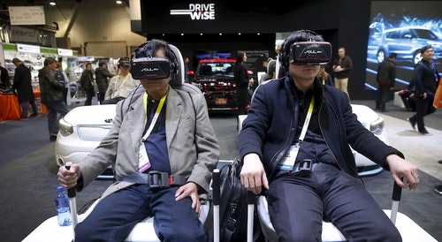 Attendees sit in a virtual reality simulator as they watch a VR movie featuring an autonomous Kia Soul at the Kia booth during the 2016 CES trade show in Las Vegas