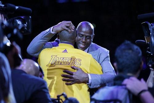 Los Angeles Lakers forward Kobe Bryant, left, hugs Magic Johnson during a ceremony before Bryant's last NBA basketball game, against the Utah Jazz, Wednesday, April 13, 2016, in Los Angeles. (AP Photo/Jae C. Hong)