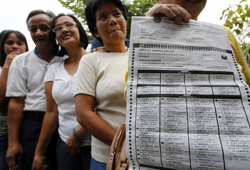 A resident shows her sample ballot while queuing to vote at a polling station in Tarlac province, in northern Philippines May 10, 2010. More than 50 million Filipinos voted for president, the highest position of the country, and nearly 18,000 other national and local positions on Monday. REUTERS/Erik de Castro (PHILIPPINES - Tags: POLITICS ELECTIONS) - RTR2DOIE