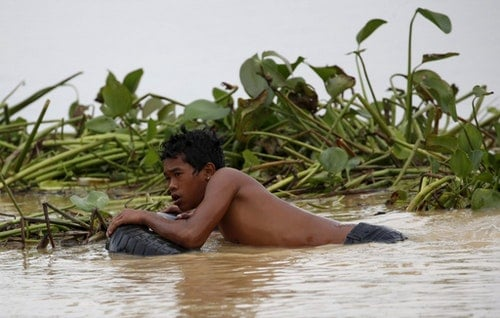 A farmer uses a tyre as a float as he tries to remove water lilies in a flooded rice field in Jaen, Nueva Ecija in northern Philippines October 20, 2015, after the province was hit by Typhoon Koppu. A typhoon swept across the northern Philippines killing at least nine people as trees, power lines and walls were toppled and flood waters spread far from riverbeds, but tens of thousands of people were evacuated in time. REUTERS/Erik De Castro - RTS577W