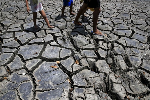 Residents walk over the cracked soil of a 1.5 hectare dried up fishery at the Novaleta town in Cavite province, south of Manila May 26, 2015. President Benigno Aquino III approved the proposal of the National Food Authority (NFA) to import further 250,000 tonnes of rice as the drought-inducing El Nino weather phenomenon continue to affect farmlands in the provinces resulting to more damaged crops. REUTERS/Romeo Ranoco - RTX1EJE5
