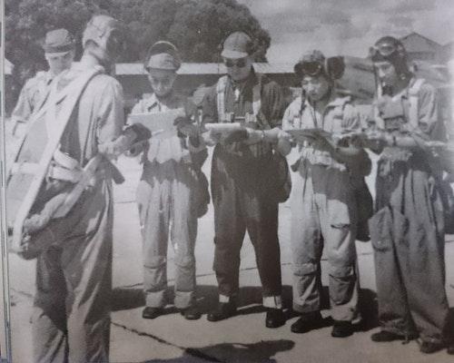準備出動的國軍飛行員,有人戴飛行帽、有人戴工作帽夾耳機,揹座式傘,穿連身飛行衣不紮褲管