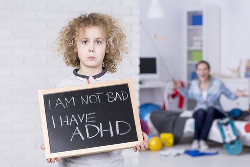 Sad ADHD boy holding small board, shouting mother in background