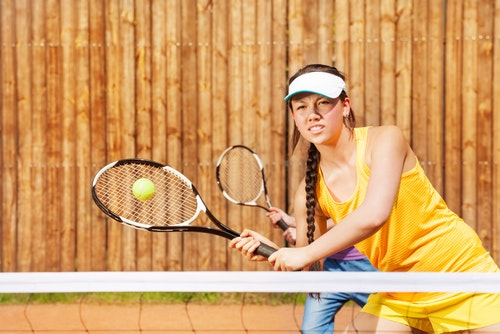 Determined female tennis player playing match on the court in summer