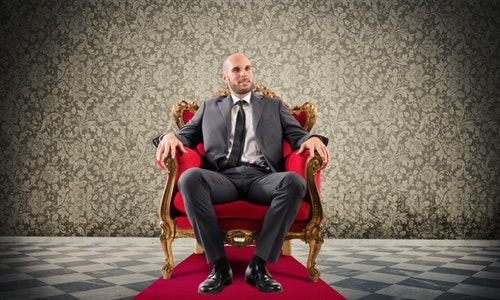 Successful businessman sitting on a royal armchair