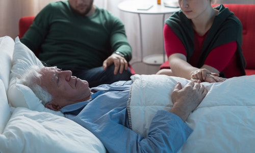 Adult children saying goodbye with aged dying father in hospital