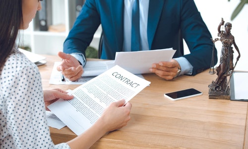 Cropped_shot_of_lawyer_holding_papers_an