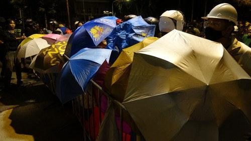 泰國抗議民眾撐起雨傘備戰