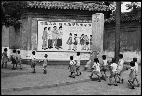 07_亨利.卡蒂耶-布列松,《孩童正從一幅寫著「…媽媽們都是上學去…」宣傳標語的